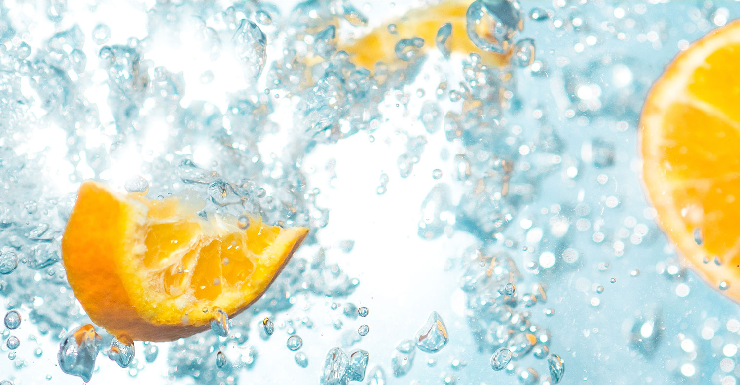 splashing water in the air with pieces of oranges