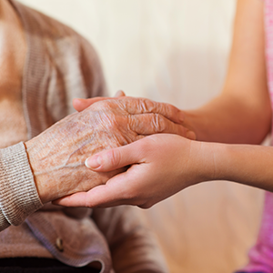elderly woman and her caregiver holding hands