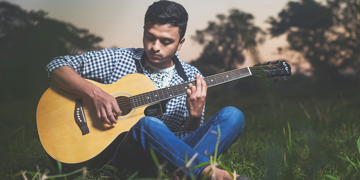 A man playing guitar in a park