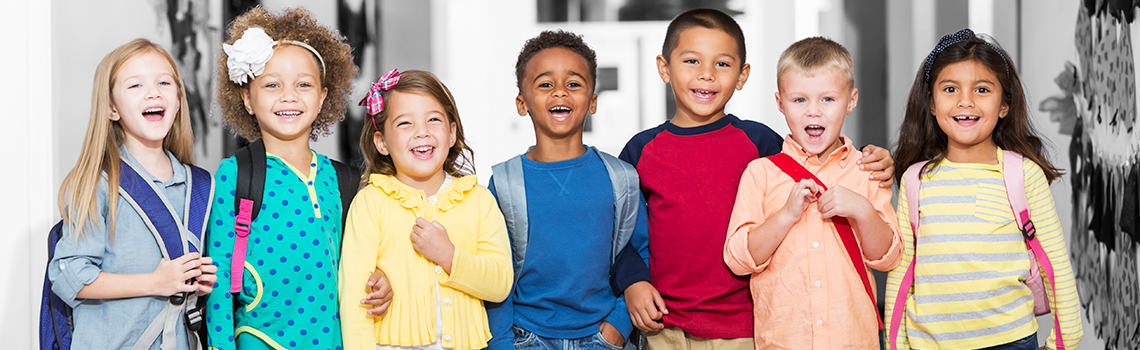 Children smiling and wearing backpacks