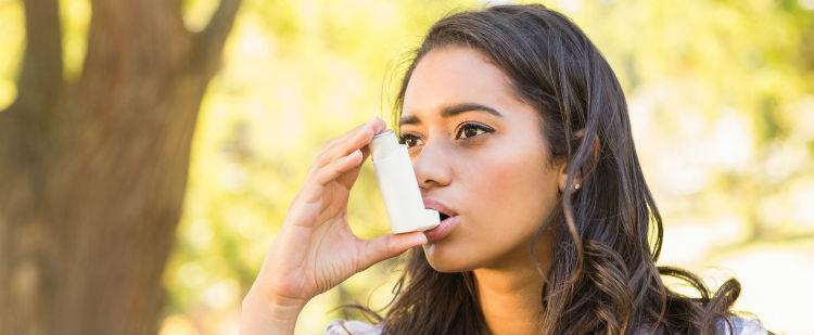 Girl using asthma inhaler