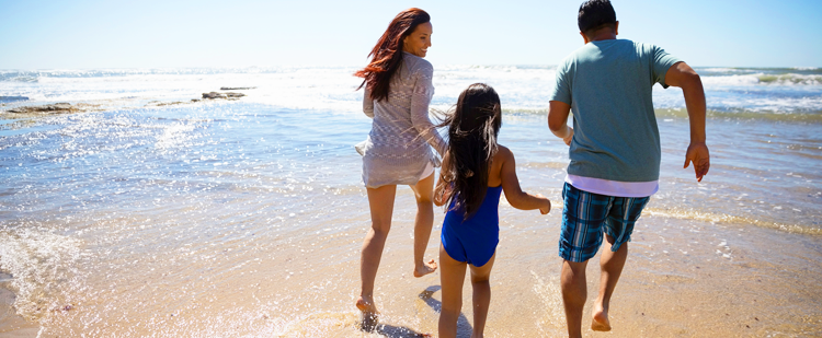 A mom, dad and daughter running on the beach towards the water