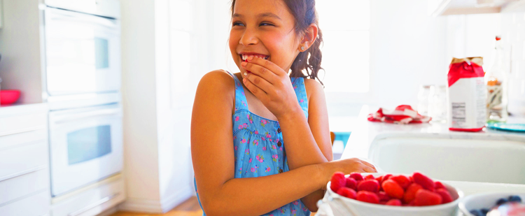 a young girl eating strawberries in the kitchen