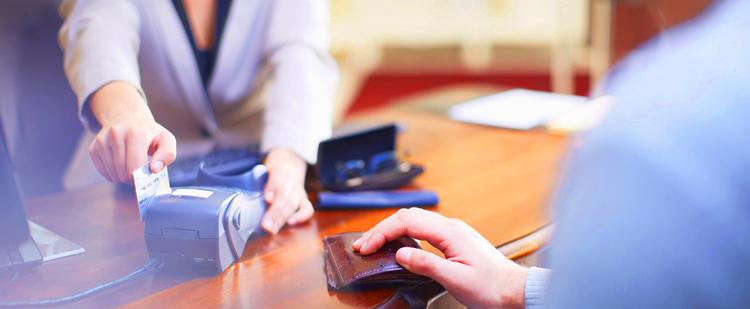 A man making a payment as a woman slides credit card through a machine