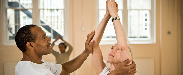 trainer helping a senior with her stretching