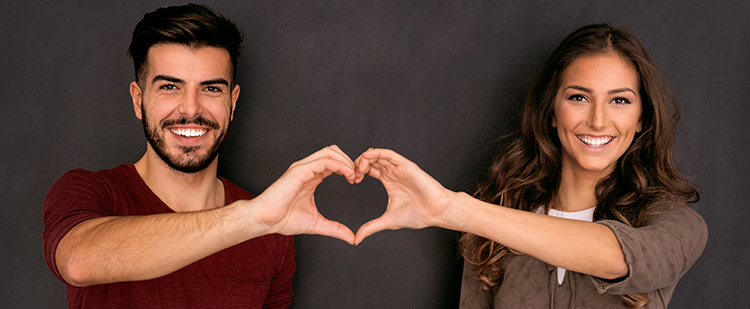 two people making the shaping of one heart with their hands
