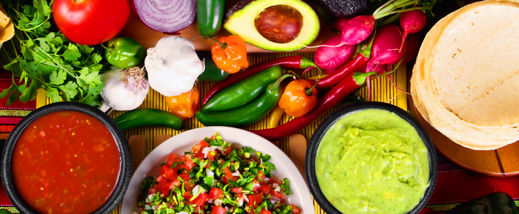 fresh fruits and vegetables on a table with bowls of salsa, guacamole and pico de gallo