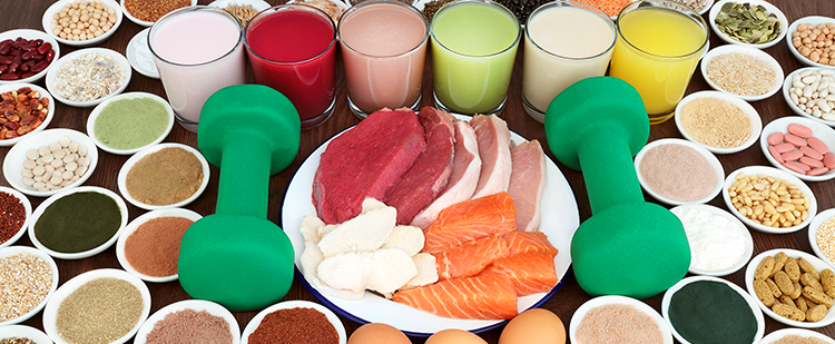 a tabletop full of small dishes containing spices, pills, beans that surround a plate of different meats. the plate has two dumbbells on the side and six glasses of different colored juices
