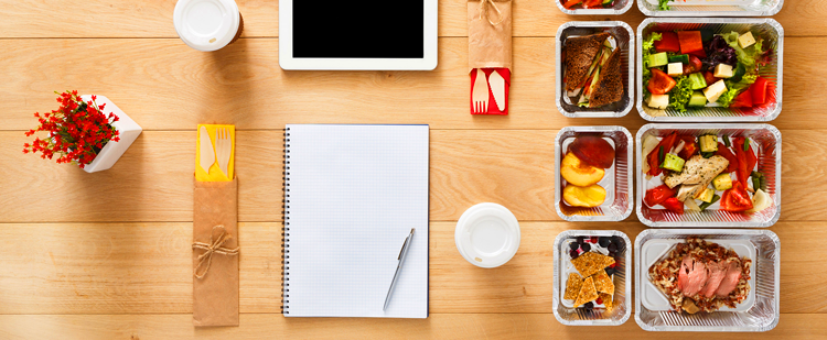 a table top setting with pans of healthy food, a notebook, an iPad and drinks