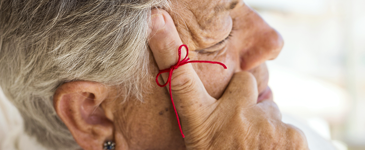 a senior woman with her hand on her face, a red string is tied to her finger