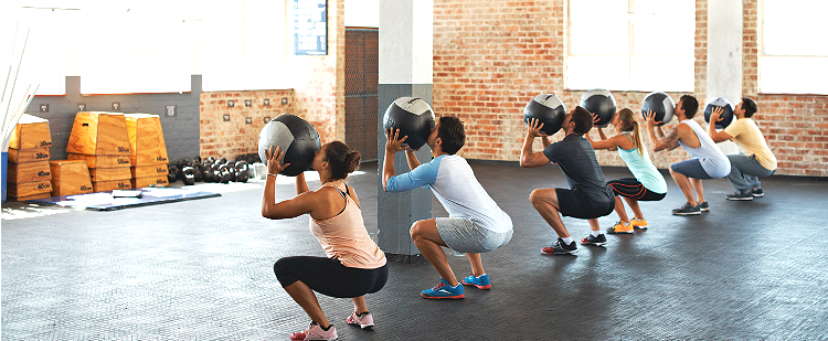 Men and women in exercise class lifting medicine balls