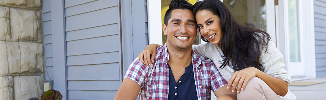 a couple sitting on a porch and smiling at the camera
