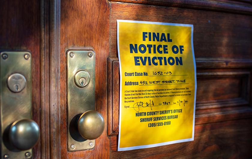 Eviction notice on door of house with brass door knob.
