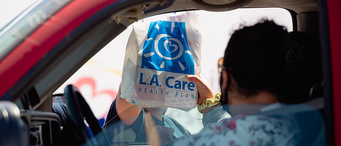 woman receiving L.A. Care bag in her car