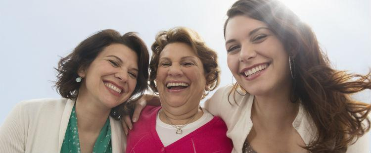 Three generations of women smile into the camera