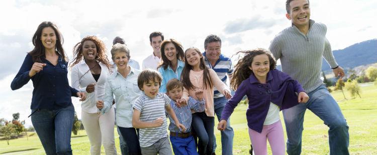 Multi-generational Hispanic family runs in a park