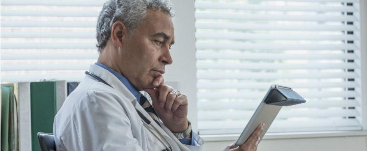 Health Care Provider reviewing electronic health record on tablet