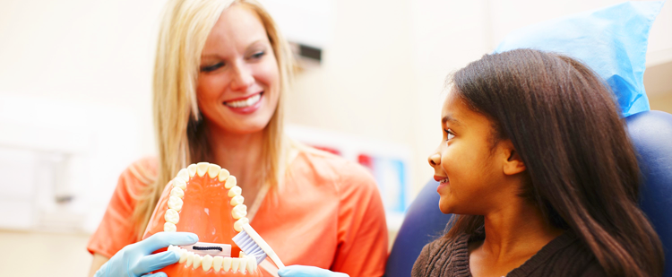 Dentist showing a young girl how to brush teeth