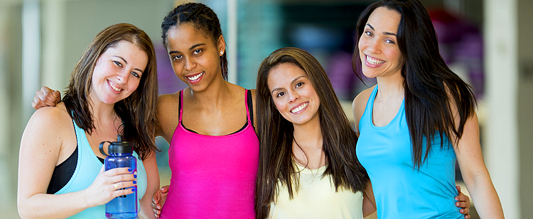 four female friends standing with arms around each other after exercise class
