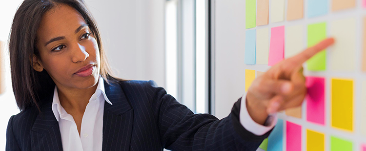 a woman in a business suit pointing to a board with post-its on it