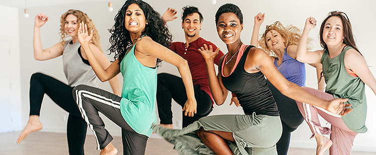 Participants in an exercise class doing cardio dance