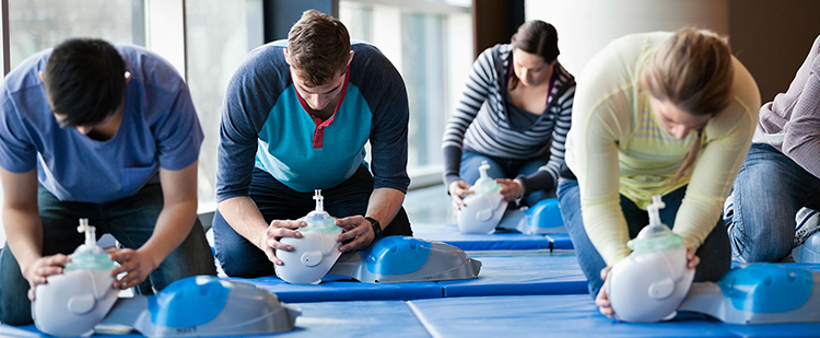participants in a CPR class practicing with equipment on the mat