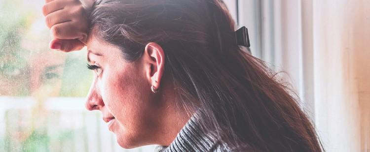 Woman looking out window with hand on forehead